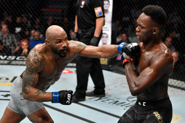 Yoel Romero of Cuba punches Israel Adesanya of Nigeria in their UFC middleweight championship fight during the UFC 248 event at T-Mobile Arena on...