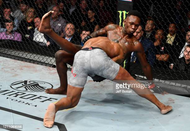 Yoel Romero of Cuba takes down Israel Adesanya of Nigeria in their UFC middleweight championship fight during the UFC 248 event at TMobile Arena on...