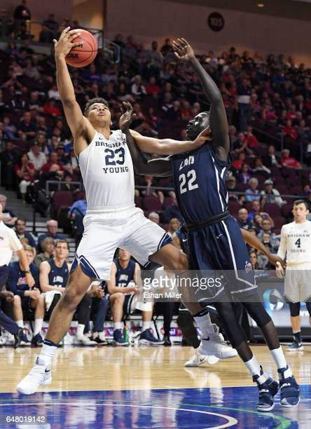 Yoeli Childs of the Brigham Young Cougars and Buay Tuach of the Loyola Marymount Lions go after a loose ball during a quarterfinal game of the West...