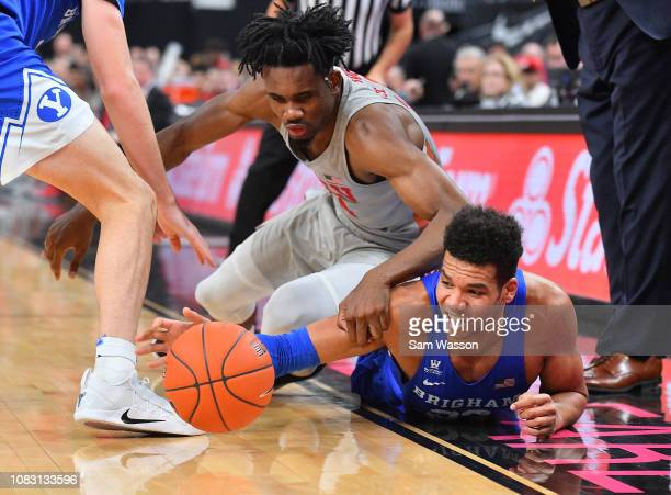 Yoeli Childs of the Brigham Young Cougars and Joel Ntambwe of the UNLV Rebels scramble for a loose ball during their game at TMobile Arena on...