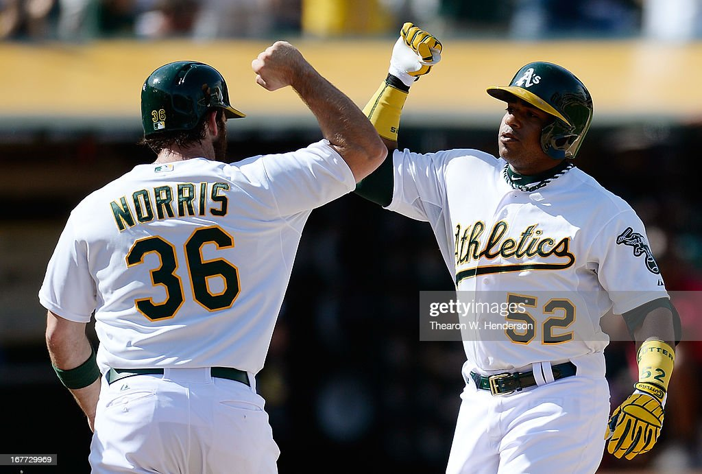 Yoenis Cespedes #52 and Derek Norris #36 of the Oakland Athletics celebrates at home plate after Cespedes hit a two-run home run with two out in the ninth inning to tie the game 8-8 against the Baltimore Orioles at O.co Coliseum on April 28, 2013 in Oakland, California.
