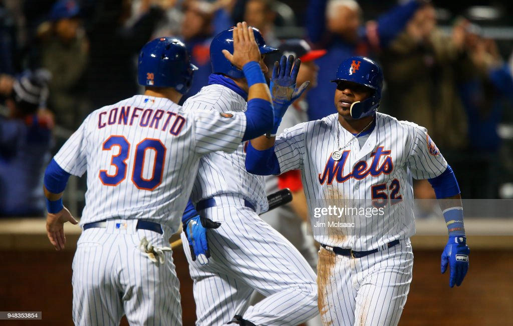 Yoenis Cespedes #52 and Michael Conforto #30 of the New York Mets celebrate after both scored in the eighth inning against the Washington Nationals at Citi Field on April 18, 2018 in the Flushing neighborhood of the Queens borough of New York City.