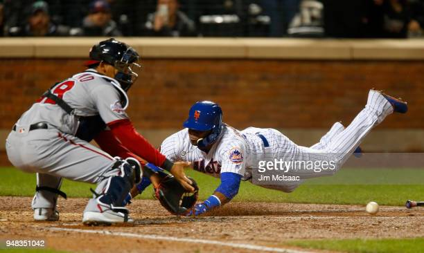 Yoenis Cespedes of the New York Mets dives home for a run in the eighth inning ahead of the throw to Pedro Severino of the Washington Nationals at...