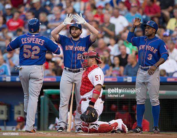 Yoenis Cespedes of the New York Mets is greeted by Daniel Murphy and Curtis Granderson after his two run home run in the top of the first inning...