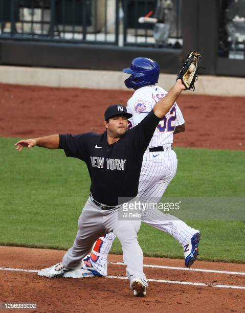 Yoenis Cespedes of the New York Mets is out at first against Mike Ford of the New York Yankees during their Pre Season game at Citi Field on July 18,...
