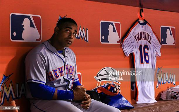 Yoenis Cespedes of the New York Mets looks on from the dugout where he had hung a Jose Fernandez jersey in honor of the late pitcher during the game...