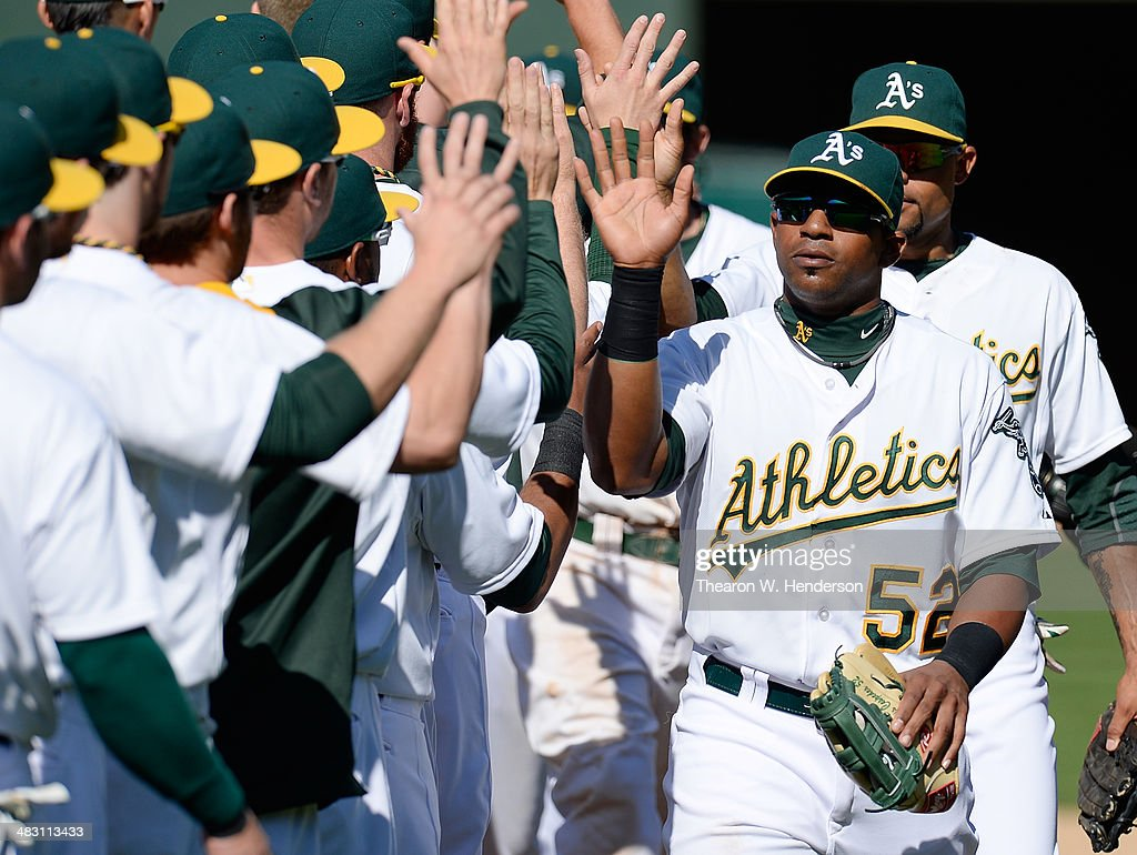 Yoenis Cespedes #52 of the Oakland Athletics celebrates with his teammates defeating the Seattle Mariners 6-3 at O.co Coliseum on April 6, 2014 in Oakland, California.