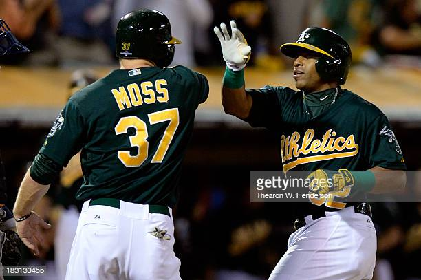 Yoenis Cespedes of the Oakland Athletics celebrates with teammate Brandon Moss after hitting a two run home run in the seventh inning against Max...