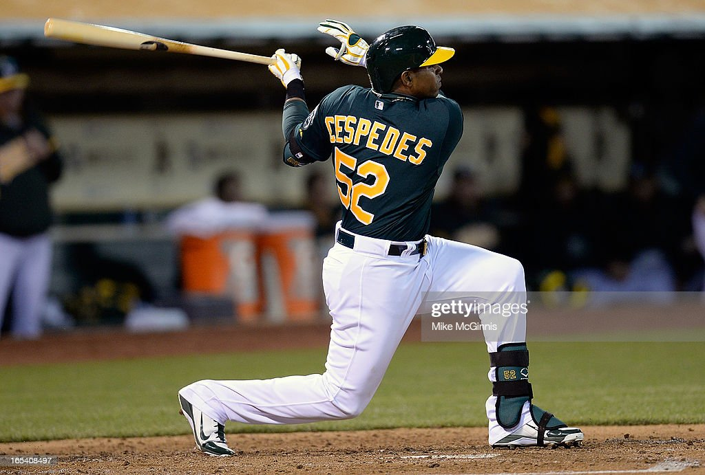 Yoenis Cespedes #52 of the Oakland Athletics hits a sacrifice fly, driving in Coco Crisp against the Seattle Mariners in the third inning at O.co Coliseum on April 3, 2013 in Oakland, California.