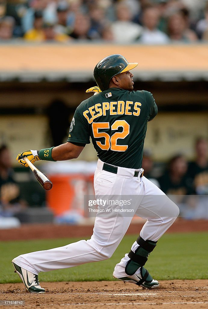Yoenis Cespedes #52 of the Oakland Athletics hits an RBI single scoring Coco Crisp #4 in the third inning against the Cincinnati Reds at O.co Coliseum on June 25, 2013 in Oakland, California.
