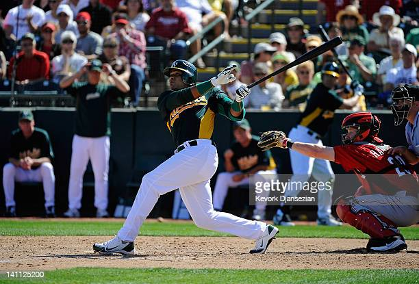 Yoenis Cespedes of the Oakland Athletics hits his first home run of the spring against the Cincinnati Reds during a spring training baseball game at...
