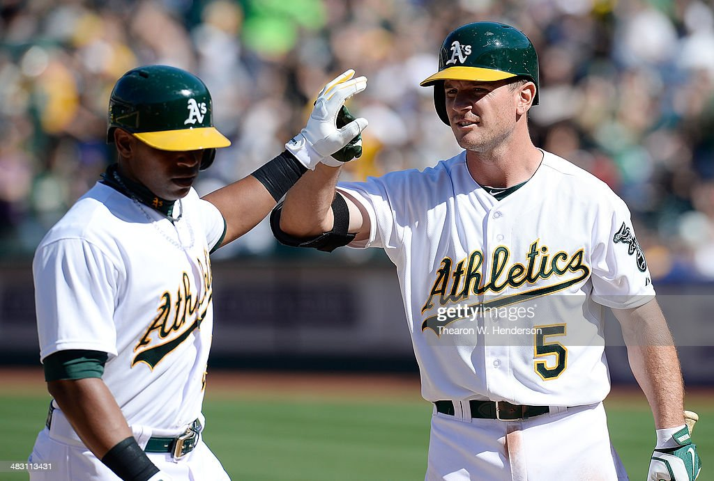 Yoenis Cespedes #52 of the Oakland Athletics is congratulated by John Jaso #5 after Cespedes hit a solo home run against the Seattle Mariners in the bottom of the eighth inning at O.co Coliseum on April 6, 2014 in Oakland, California. The Athletic won the game 6-3.