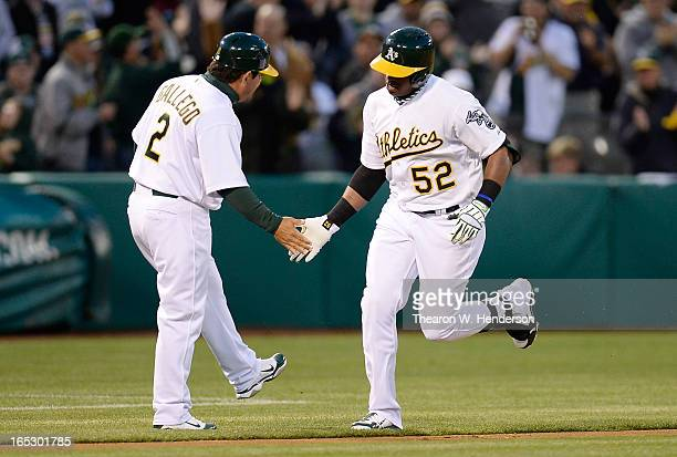 Yoenis Cespedes of the Oakland Athletics is congratulated by third base coach Mike Gallego after Cespedes hit a solo home run against the Seattle...