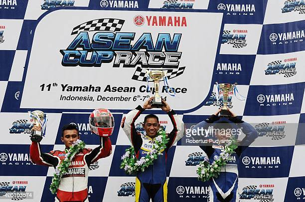 Yoga Adi of Indonesia Mohd Affendi bin Rosli of Malaysia and Peerapong Luiboonpeng of Thailand celebrate on the podium at the end of MT class race...