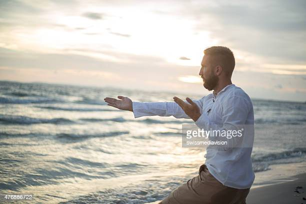 Yoga and tai chi position on the beach at sunset