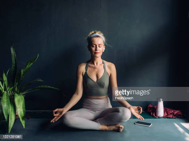 yoga at home: beautiful blonde woman meditating in the lotus position while listening to music - lotus position stock pictures, royalty-free photos & images