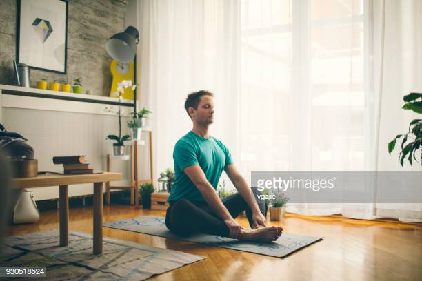 yoga at home - meditating stock pictures, royalty-free photos & images