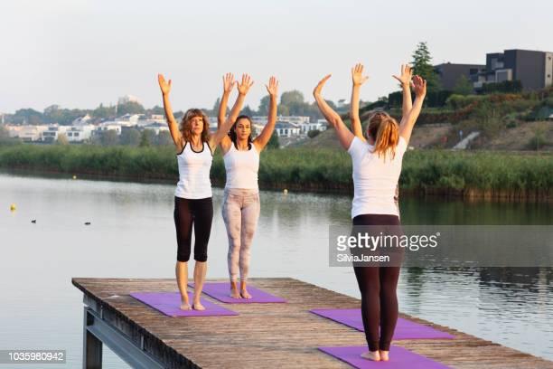 Yoga-Kurs bei Sonnenaufgang: der Sonnengruß am städtischen See zu tun