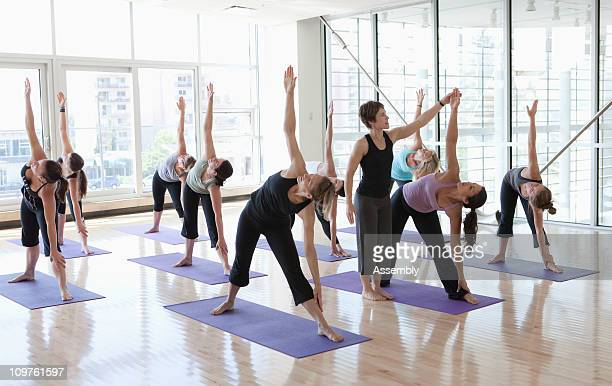 yoga class being led by instructor - yoga teacher stock pictures, royalty-free photos & images