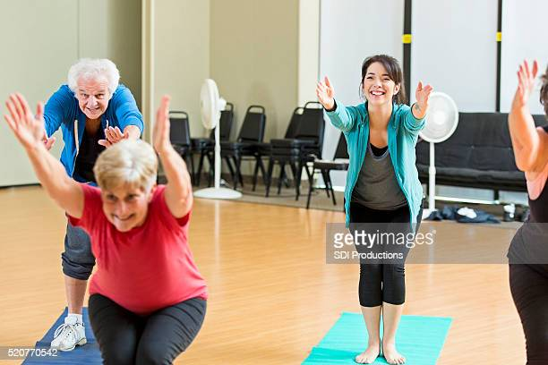 Yoga class demonstrates chair pose