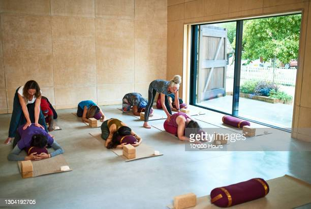 yoga class in child's pose with instructors helping - human back stock pictures, royalty-free photos & images