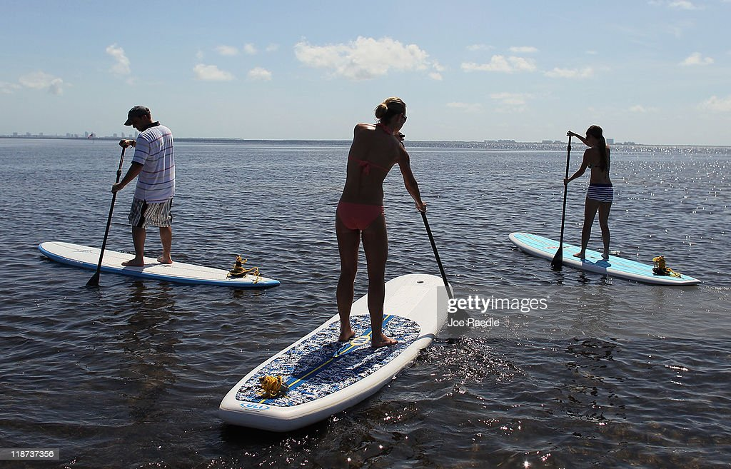 Yoga class participants paddle their boards to a yoga session at Adventure Sports Miami on July 10, 2011 in Miami, Florida. The paddle board is said to give the body's core more of a workout then in a gym since the platform is unstable and one must use the muscles to remain balanced on the board.