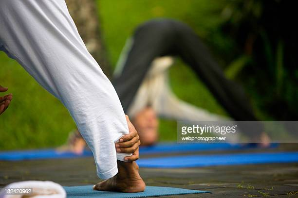yoga class - teacher bending over stock photos and pictures