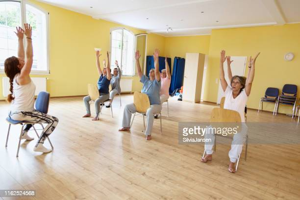 yoga class: senior women exercising on chair - chair stock pictures, royalty-free photos & images