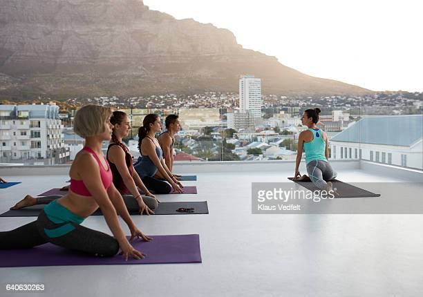 Yoga class stretching at sunset on rooftop