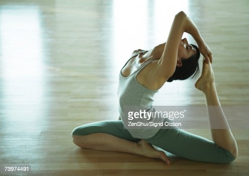 yoga class woman doing onelegged king pigeon pose highres