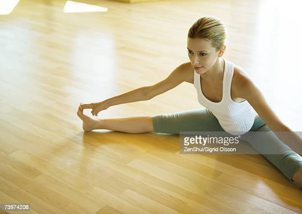 yoga class, woman sitting with legs apart, touching toes - legs apart stock pictures, royalty-free photos & images
