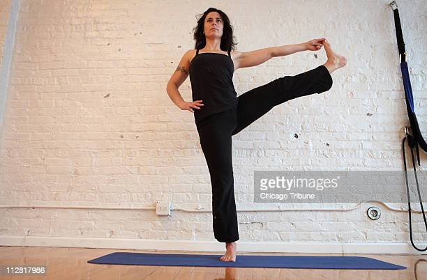 Yoga devotee Sara Walther wears a pair of Lululemon yoga pants with an Athleta convertible top to practice yoga at Moksha Yoga Center in Chicago...