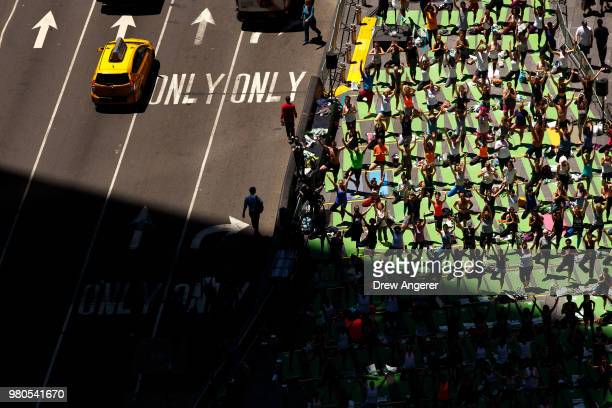 Yoga enthusiasts participate in a mass yoga class in Manhattan's Times Square to celebrate the summer solstice and mark World Yoga Day June 21 2018...