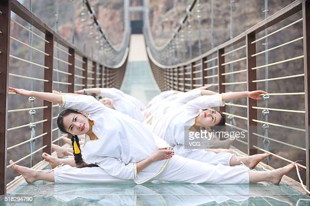 Yoga enthusiasts pose on the glass suspension bridge at Fuxishan Tourism Resort on March 30 2016 in Zhengzhou Henan Province of China People did yoga...