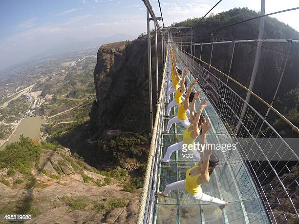 Yoga enthusiasts practice on a glass suspension bridge at the Shiniuzhai National Geological Park on November 5, 2015 in Pingjiang County, Yueyang...