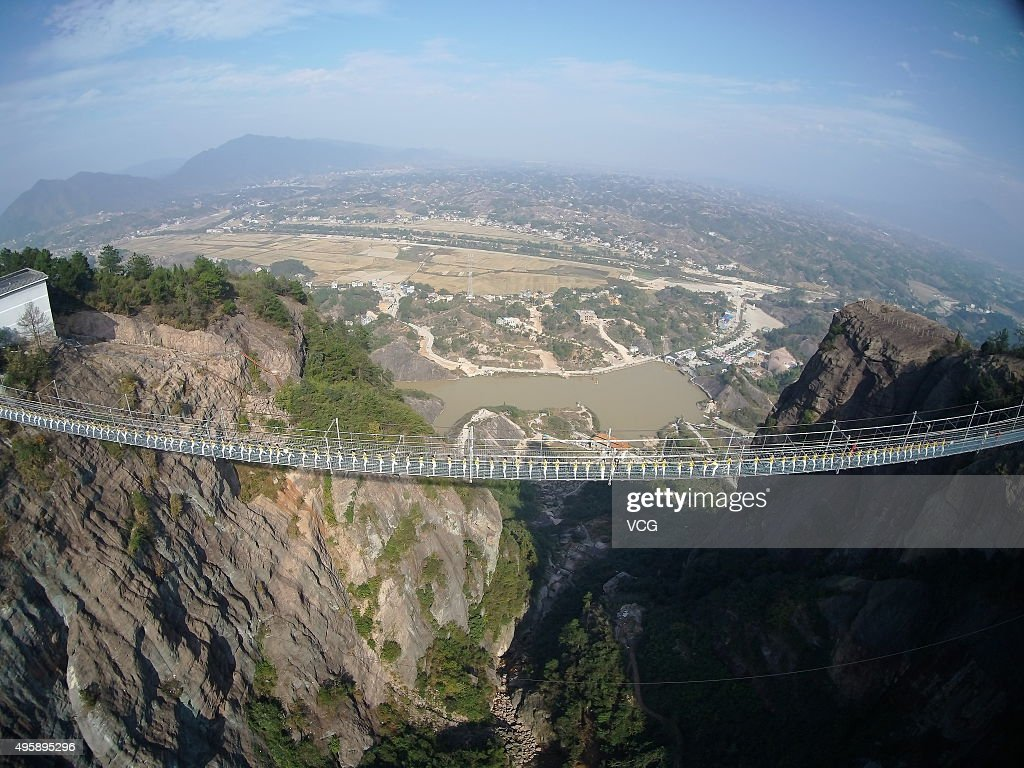 Yoga enthusiasts practice on a glass suspension bridge at the Shiniuzhai National Geological Park on November 5, 2015 in Pingjiang County, Yueyang City, Hunan Province of China. 100 yoga enthusiasts practice on the glass suspension bridge with a length of 300 meters and a maximum height of 180 meters at the Shiniuzhai National Geological Park in Pingjiang.