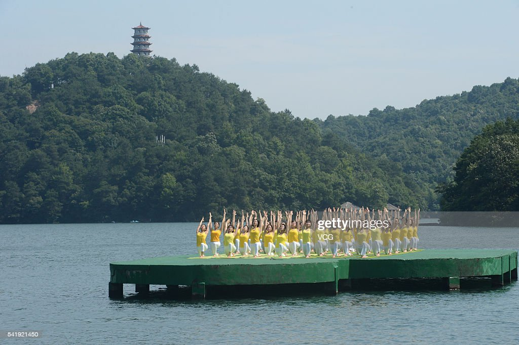 Yoga enthusiasts practice yoga on the water of Shiyan Lake on June 21, 2016 in Changsha, Hunan Province of China. About 100 yoga enthusiasts perform yoga to welcome the International Day of Yoga which falls on June 21 each year.
