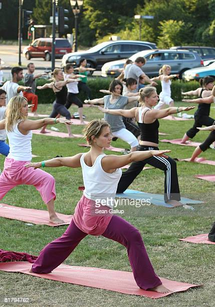 Yoga enthusiasts take part in the 'Urban Yoga KickOff' at the Victory Column in Tiergarten Park as traffic drives past on July 1 2008 in Berlin...