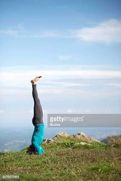 Yoga exercises in nature on mountains: headstand
