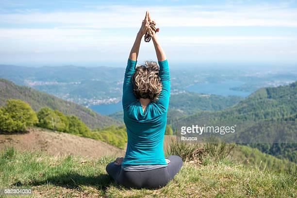 Yoga exercises in nature on mountains: Padmasana