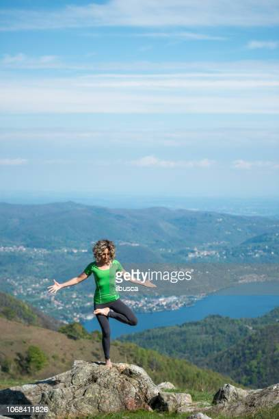 Yoga exercises in nature on mountains: tree pose