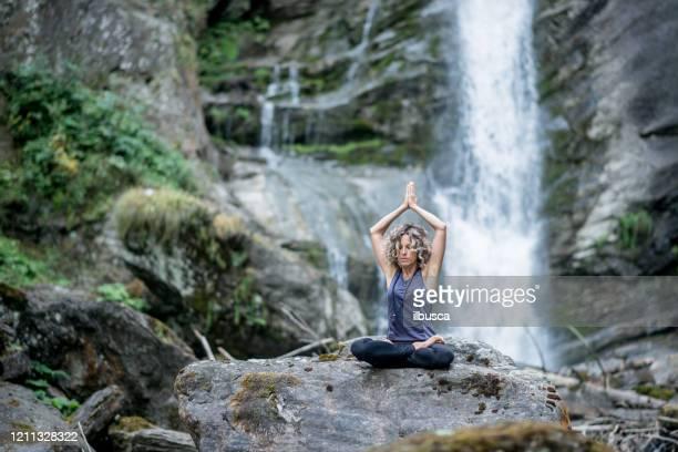 yoga exercises in nature: padmasana or lotus position - ilbusca foto e immagini stock