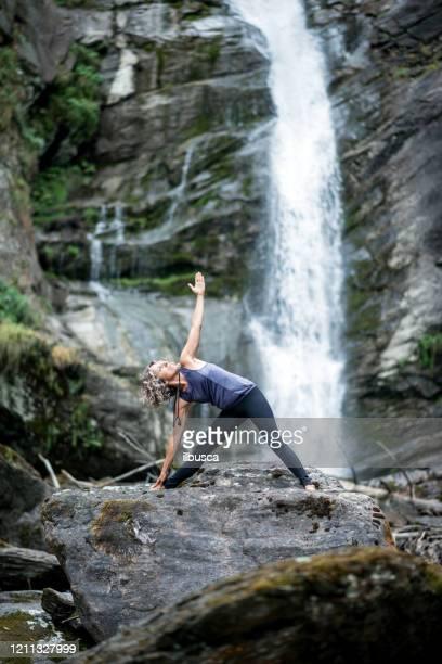 yoga exercises in nature: triangle pose - ilbusca foto e immagini stock