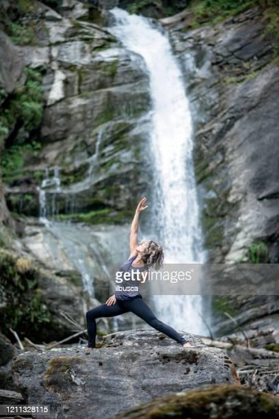 yoga exercises in nature: warrior pose - ilbusca foto e immagini stock