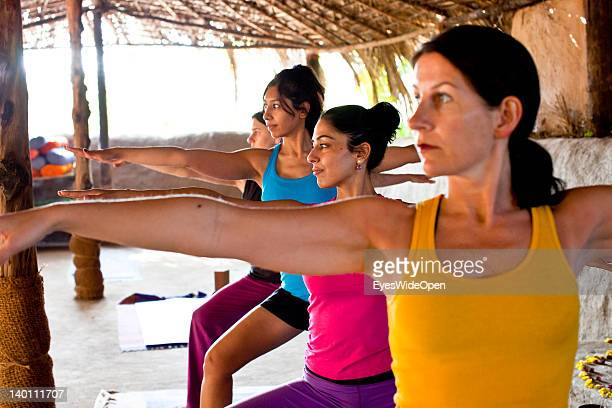 Yoga female tourists practice yoga postures and asanas with a teacher in a class in a traditional yoga shala at Yoga Magic Eco Retreat in Anjuna on...