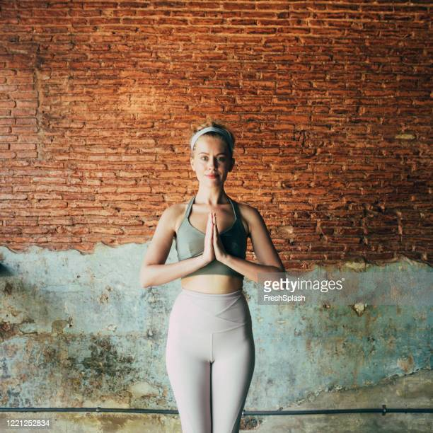yoga for inner peace: woman in the namaste yoga position - sportswear stock pictures, royalty-free photos & images