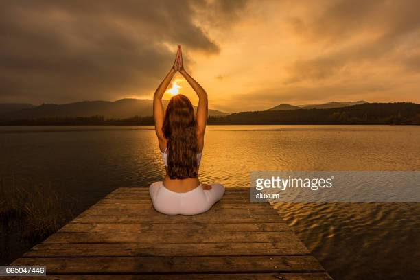 yoga in lotus pose at sunset - yogi stock photos and pictures