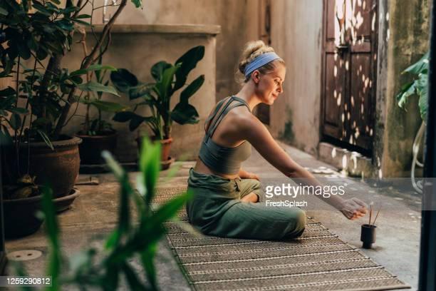 yoga in the garden: a woman doing yoga while enjoying the scent of natural incense sticks - zen imagens e fotografias de stock