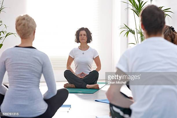 Profesor de Yoga y estudiantes Meditando
