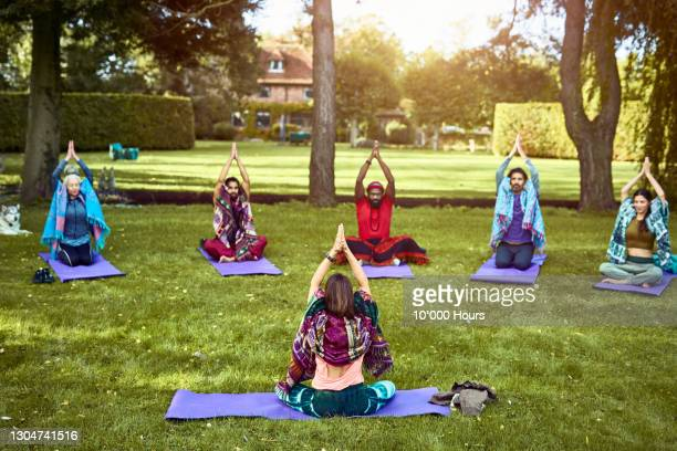 yoga instructor and students practising outdoors with arms raised - limb body part stock pictures, royalty-free photos & images